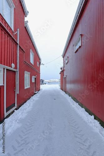 Papiers peints Ruelle etroite Snowy narrow alley between red port warehouses. Hamnoy-Reine-Lofoten-Norway. 0391