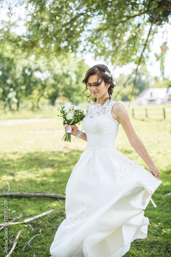 likable and pretty bride in a white wedding dress with a wedding bouquet in his hands on a enjoying romantic moments outside on a summer meadow. wedding day