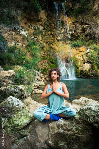 Fotobehang School de yoga young woman practice yoga outdoor on the rocks by the waterfall