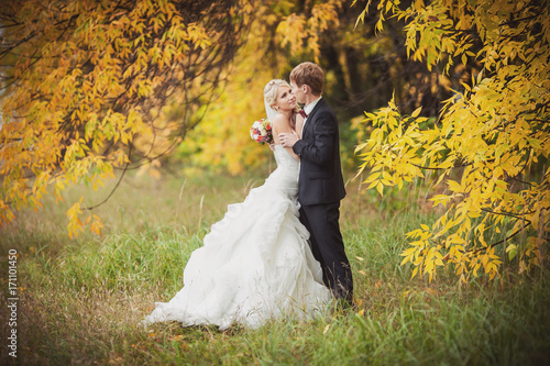 Wedding autumn. Bride and groom in autumn forest