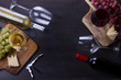 Bottles of red and white wine with wine glasses and grape on table with copy space