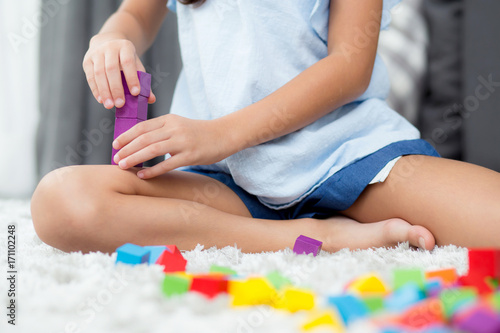 Close up of hand child playing with colorful plastic block at floor. Early learning developing to children with toys.
