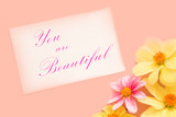 Pastel color greeting card with pink and yellow flowers and with text you are beautiful. Top view. - 171129283