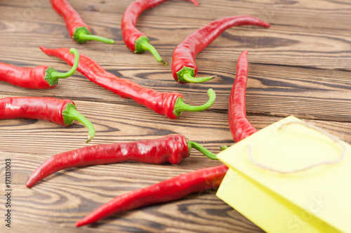 Fotobehang Hot chili peppers Wholes red fresh ripe chili pepper poured out of yellow paper bag on old brown wooden rustic planks