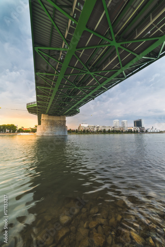 Aluminium Bruggen By the River under the Bridge. Skyline of Bratislava, Slovakia at Sunset in Background.
