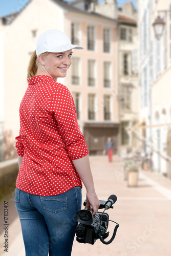 Poster woman holding his professional camcorder in the street
