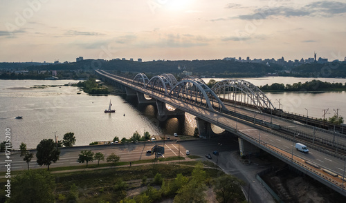 Fotobehang Kiev Aerial top view of automobile and railroad Darnitsky bridge across Dnieper river from above, Kiev (Kyiv) city sunset skyline, Ukraine