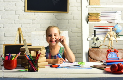 Girl with laughs and does homework on white wall background Poster
