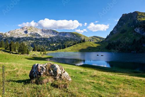Foto op Plexiglas Bergen Bergsee Seebergsee Bergmassiv Alpwiese Felsbrocken blauer Himmel Wolken