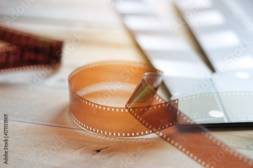 Poster Movie clapper and film strip on a wooden background