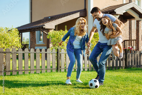 Fotobehang Voetbal Loving father carrying daughter and playing football with family