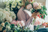 Happy beautiful young woman florist in glasses standing in flower shop - 171176015