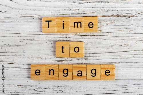 Poster time to engage word made with wooden blocks concept