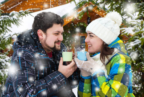 Papiers peints Cafe Attractive man with a woman drinking coffee on a background of a Christmas landscape. Winter nature