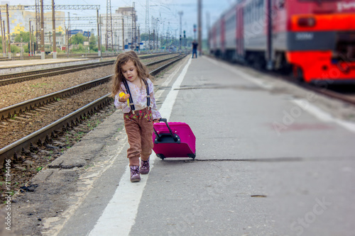 Little girl walking on railway station with the travel bag.