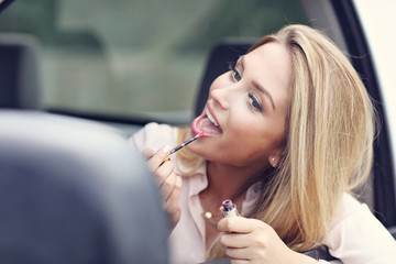 Young attractive woman looking in rear view mirror applying lipstick