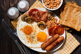 Fried eggs with bacon, sausages and vegetables, top view