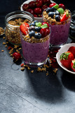 healthy blueberry with granola and fresh berries and dark background