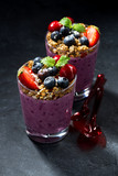 healthy dessert with granola and berries on a dark background, vertical