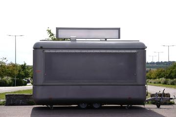 Grauer Wohnanhänger / Ein runder grauer Wohnanhänger aus Blech steht auf einem Parkplatz und dient als Verkaufsstand für Fanartikel.