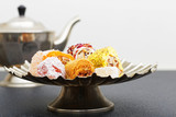 Closeup asorti of oriental sweets in a low metal vase on a dark table. Shallow focus.