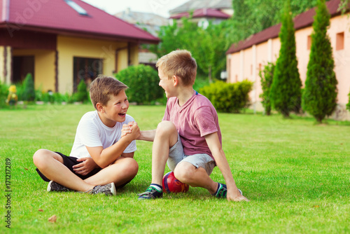Two boys having fun during playing football in schoolyard
