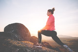 Athletic girl warming up before jogging in the mountains at sunset. Sport tight clothes.