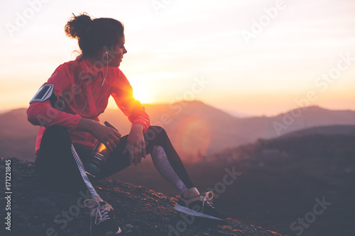 Athletic woman resting after a hard training in the mountains at sunset. Sport tight clothes. - 171221845