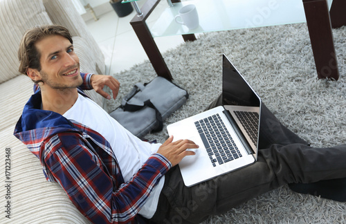 business guy with laptop sitting on carpet in living room. - 171223468