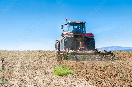 Plakat agricultural tractor in the foreground with blue sky background.