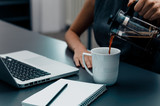 Woman hands pouring coffee into cup on office table. - 171235612