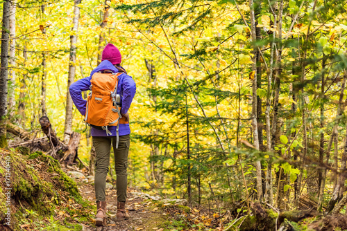 Autumn hike backpacker lifestyle woman walking on trek trail in forest outdoors with yellow leaves foliage Poster