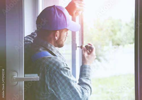 człowiek usługi instalacji okna z śrubokrętem