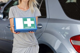 Responsibility and safety on road concept. Woman holding first aid kit for car. - 171242610