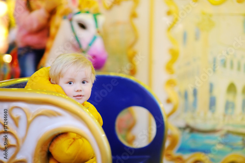 Fotobehang Amusementspark Little kid riding on colorful carousel (merry go round)