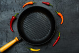 Empty grill frying pan on an dark stone table surrounded with different colorful chili peppers. Top view, flat lay - 171260666