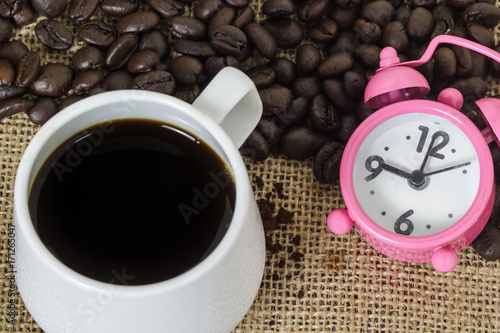 Papiers peints Cafe Hot coffee and pink clock on coffee beans background. Black coffee. Conceptual coffee and time for life style.