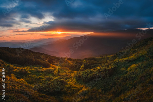 Mountain hill with stormy sky and sunbeam at sunset