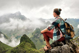 Hiker sitting on top of mountain enjoying on view of foggy mountains. - 171272469