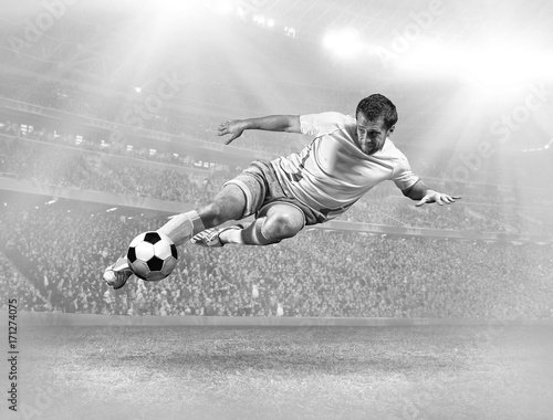 Soccer player with ball in action on field of stadium Poster