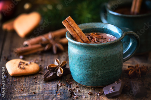 Foto op Canvas Chocolade Hot chocolate with a cinnamon stick, anise star and grated chocolate topping in festive Christmas setting on dark rustic wooden background