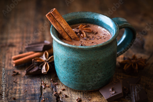 Fotobehang Chocolade Hot chocolate with a cinnamon stick, anise star and grated chocolate topping in festive Christmas setting on dark rustic wooden background