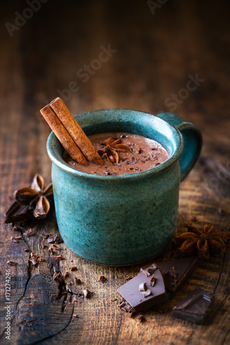 Foto op Canvas Chocolade Cup of hotchocolate with a cinnamon stick, star anise and grated dark chocolate as a topping on dark rustic wooden background