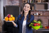 Attractive young woman holds vegetables and fruits in hands at the kitchen.