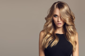 Blond woman with long curly beautiful hair. © yuriyzhuravov