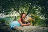 happy young woman posing on huge tree with  a bouquet of wild flowers summer in mountain - 171283482