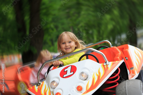 Staande foto Amusementspark happy little girl on roller coaster ride in amusement park