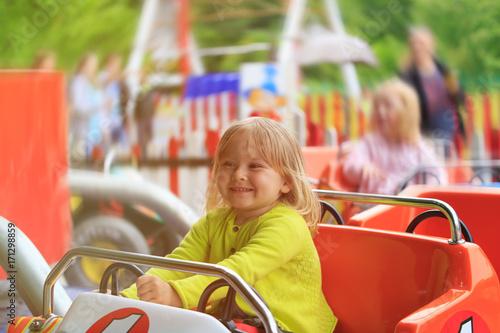 Fotobehang Amusementspark happy little girl on roller coaster ride in amusement park