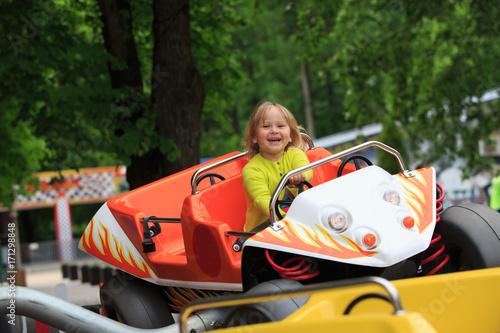 Poster happy little girl on roller coaster ride in amusement park