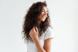 Portrait of a smiling pretty girl with curly hair looking away